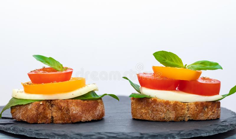 Two bruschetta Caprese on round shale board on white background with copy space. royalty free stock photography