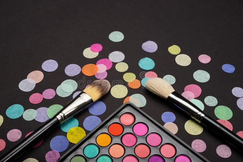 Two brushes with eyeshadow palette on back background decorated with colorful confetti. Two make-up brushes with eyeshadow palette on back background decorated royalty free stock photos