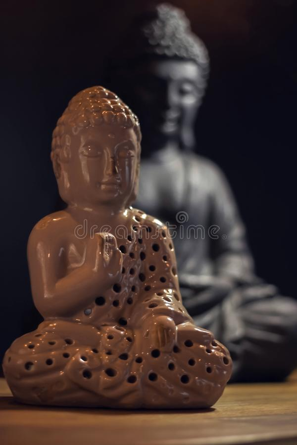 Two Buddha statuettes on a wooden table. Buddhism, meditation. stock photo