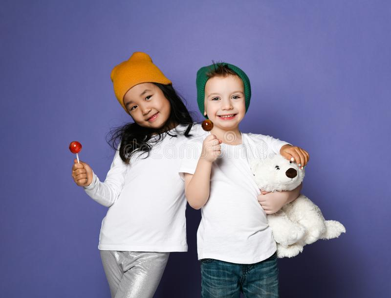 Two buddies girl and boy in colorful hats posing with thier best friend polar bear toy eating lollipop candy on purple stock photo