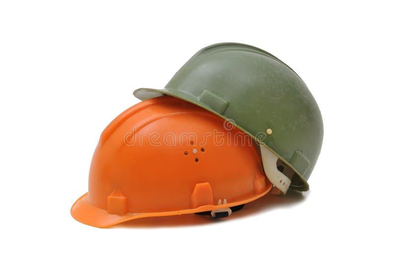 Two builders helmet. Two, orange and green builders helmet royalty free stock photos