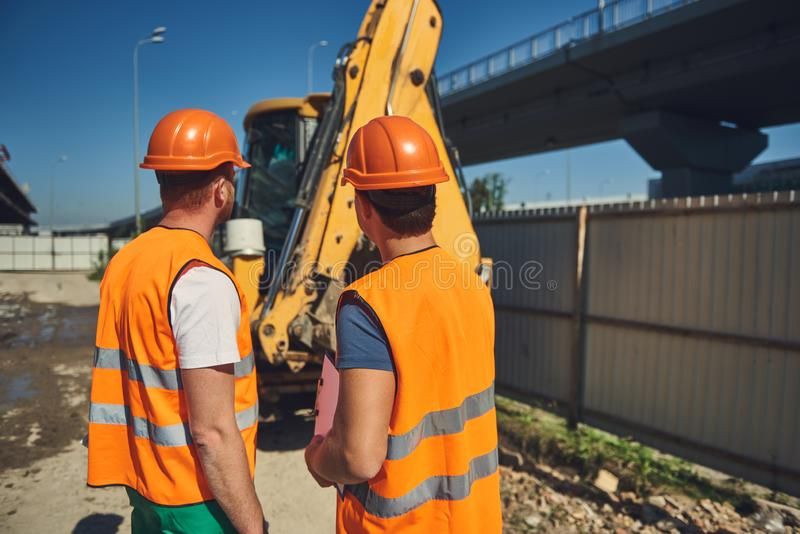 Two builders in helmets are working outdoor stock image