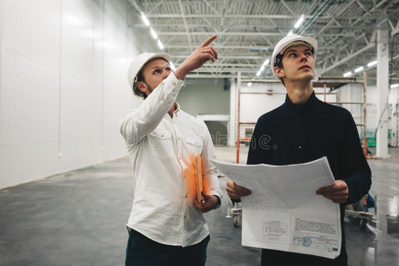 Two building engineers with blueprint working on construction site stock image