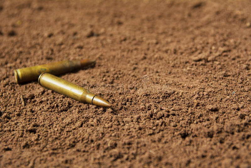 Two bullets, machine gun bullets on soil stock photography