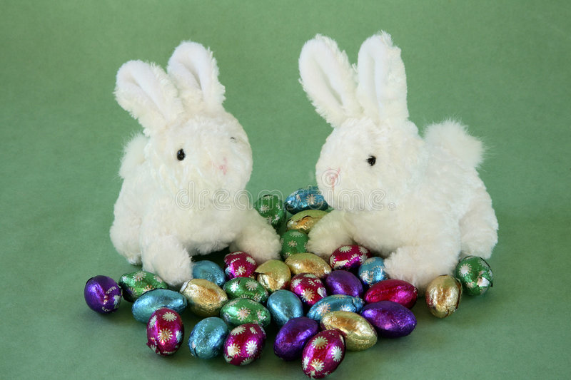 Two bunnies with miniature chocolate eggs. stock image
