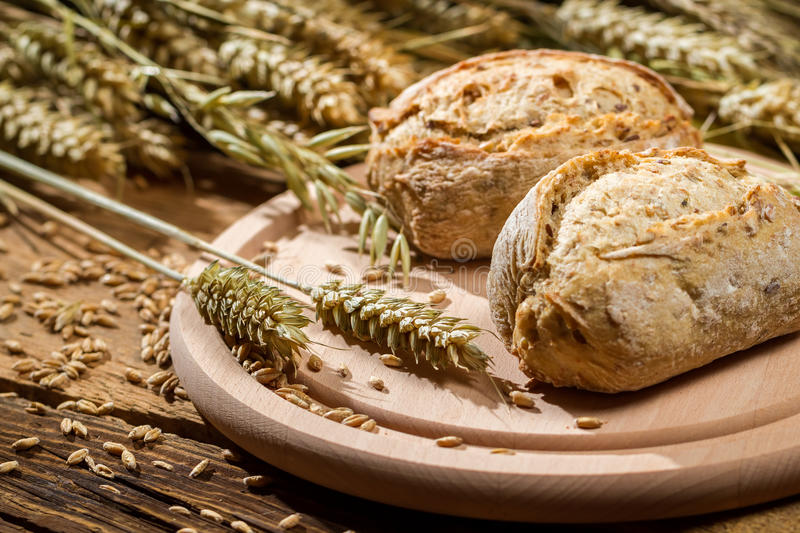 Two buns on the background of grains with ears royalty free stock image