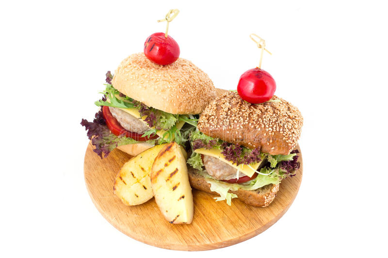 Two burgers on wooden cutting board royalty free stock photography