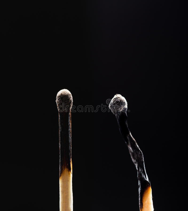 Two burned out wooden matches on black royalty free stock photo
