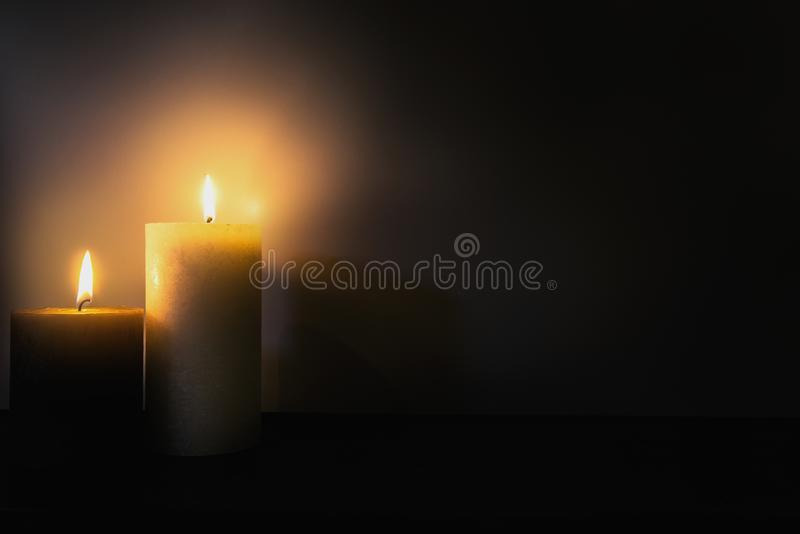 Two burning brightly candles in the dark shadow, space for text romantic colorful concept background royalty free stock images
