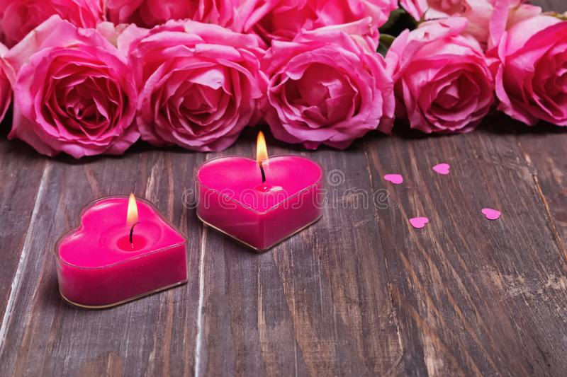 Two burning candles and beautiful pink roses on the wooden background royalty free stock image