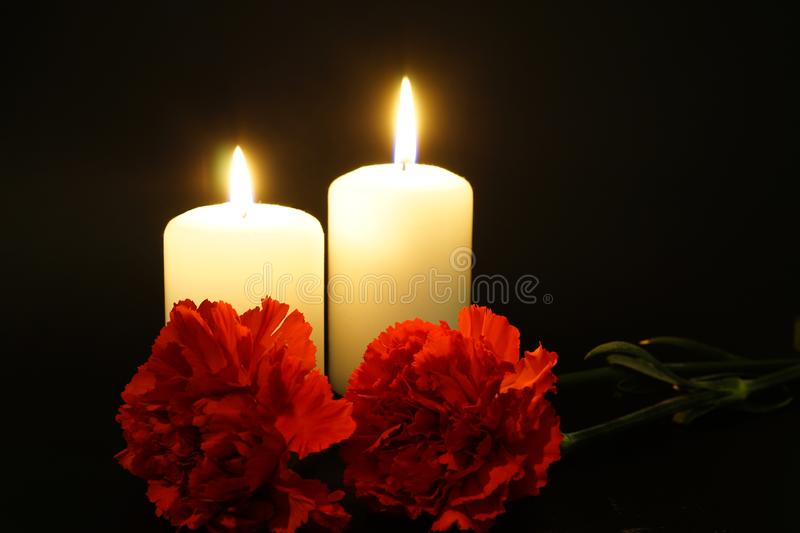 Two burning candles with flowers stock image