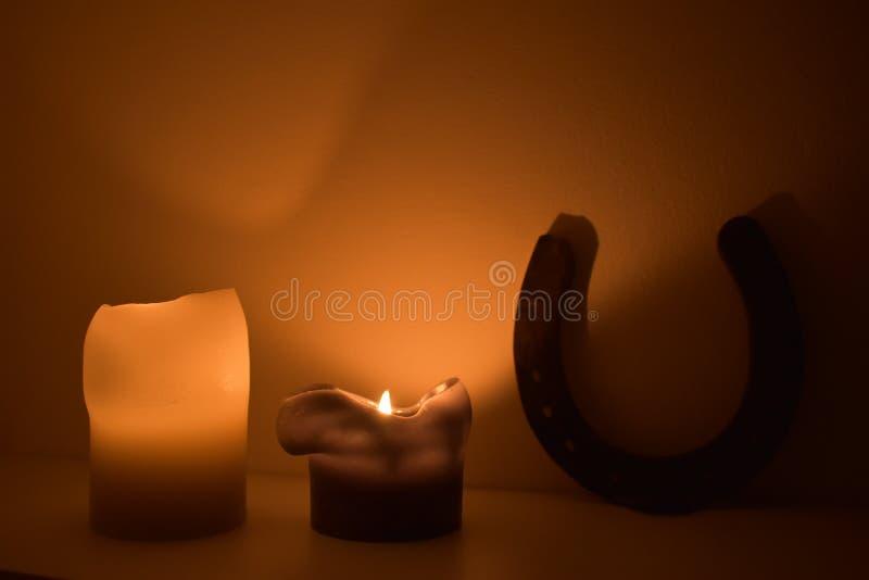 Two burning candles and horseshoe stock photos