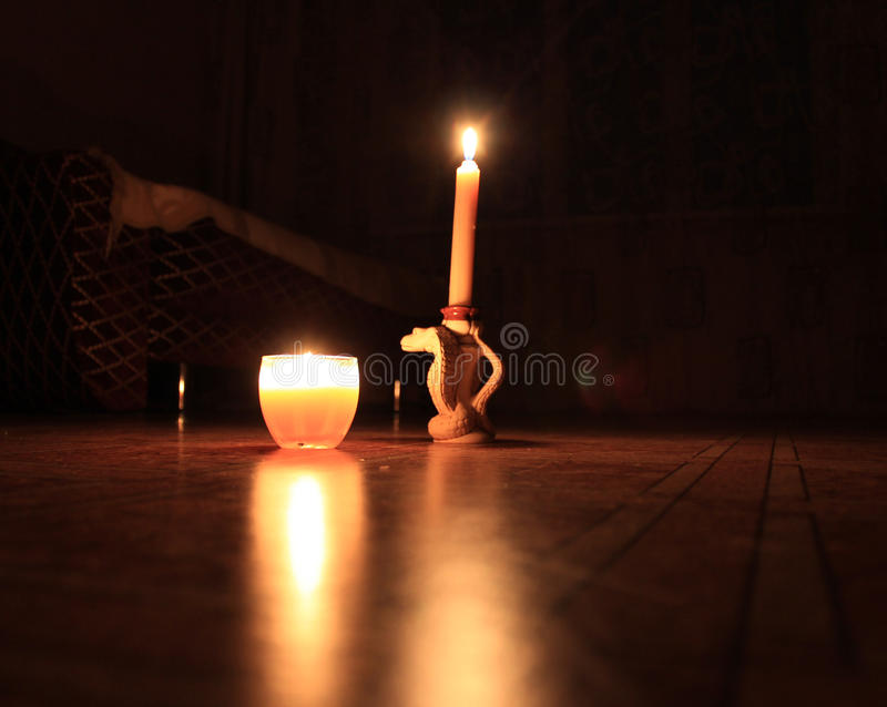 Two burning candles in the room stock images