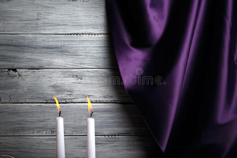 A silk purple curtain, two burning candles, romantic evening with beloved on a light gray background. stock photography