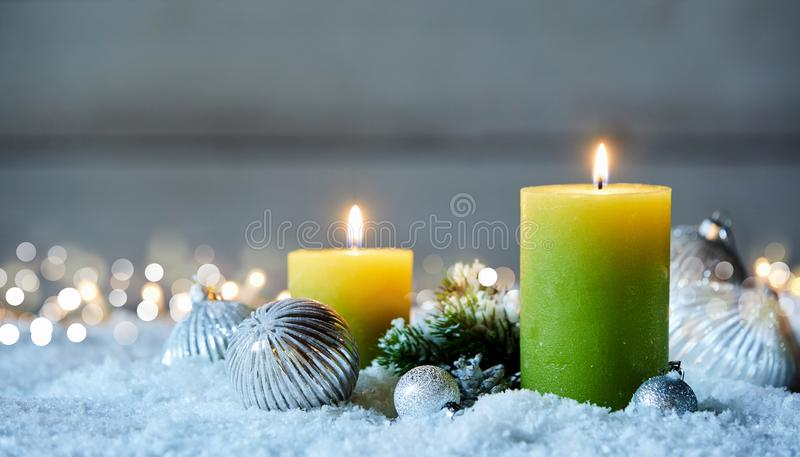 Two Christmas candles on snow. Two burning Christmas candles and decorations on snow with bokeh lights stock photos
