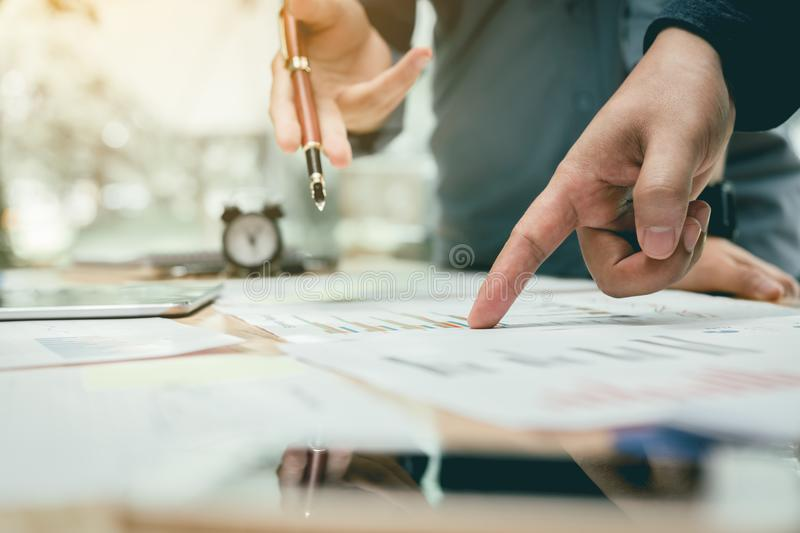 Two business asian people pointing on summary report graph and t stock images