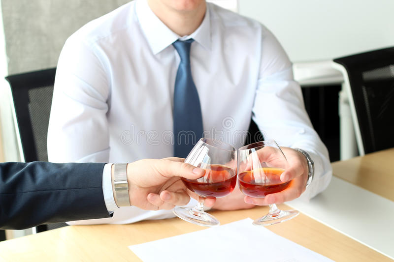 Two business colleagues celebrate signing a contract with Whisky.  stock photography