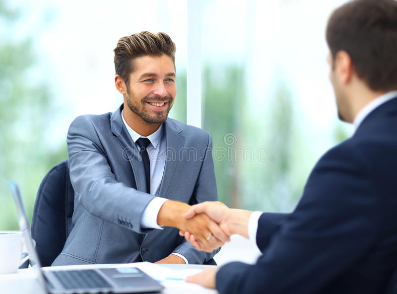 Two business colleagues shaking hands during meeting stock images