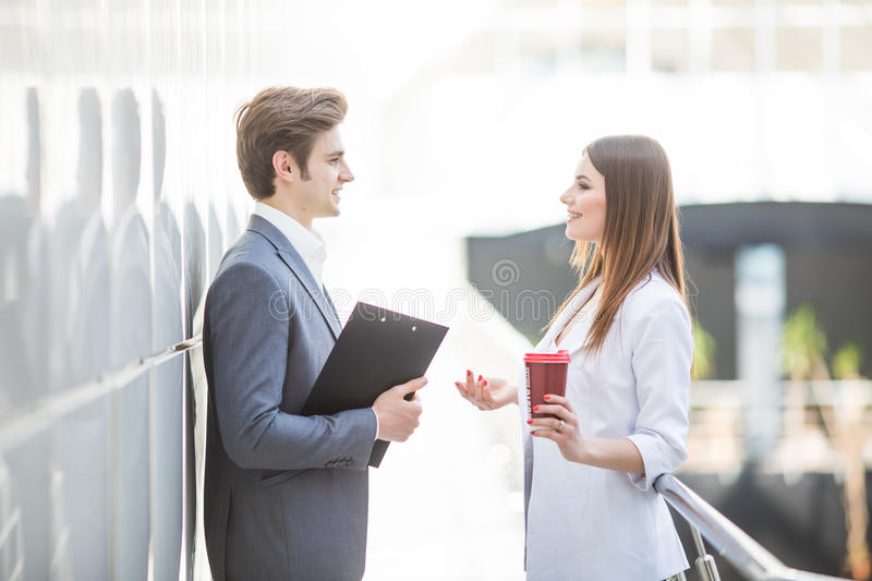 Two Business Colleagues standing in office hall having informal discussion with coffee royalty free stock image