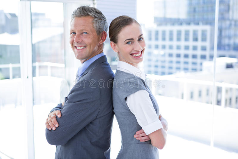 Two business colleagues standing back to back royalty free stock images