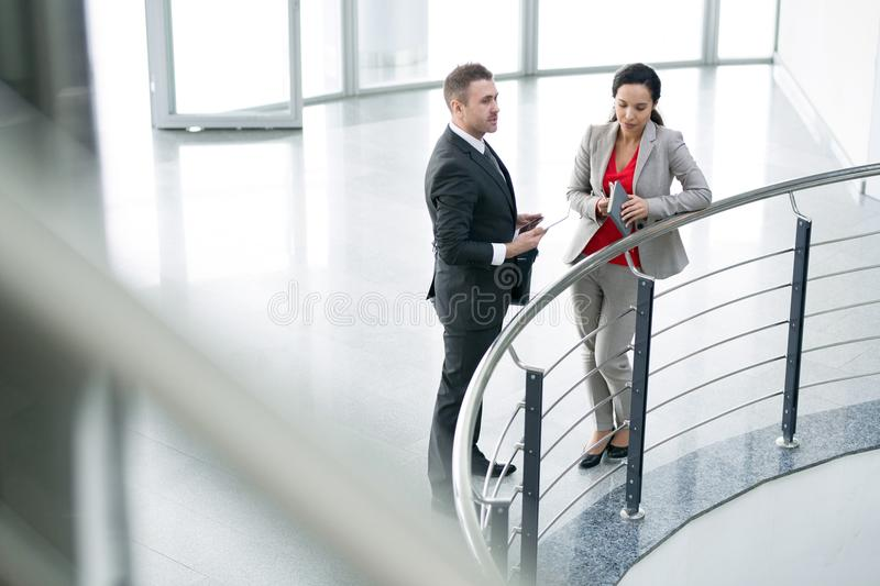 Two Business Colleagues Talking at Balcony. High angle full length portrait of two business people, men and woman, standing by rail at balcony of modern office royalty free stock photo