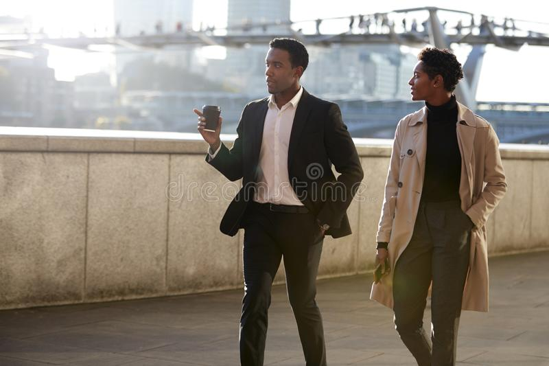 Two business colleagues walking by the Thames riverside in the city of London talking, man gesturing royalty free stock photography