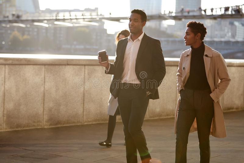 Two business colleagues walking by the Thames riverside in the city of London talking, man holding takeaway coffee royalty free stock image