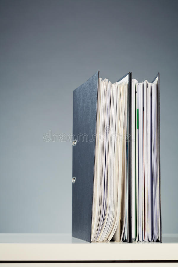 Two Business Folders with Documents. Business documents or files in two folders standing straight on a white desk surface stock photos