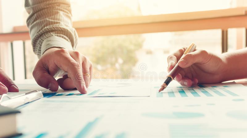 Two business hand pointing at market research on paperwork with royalty free stock photography