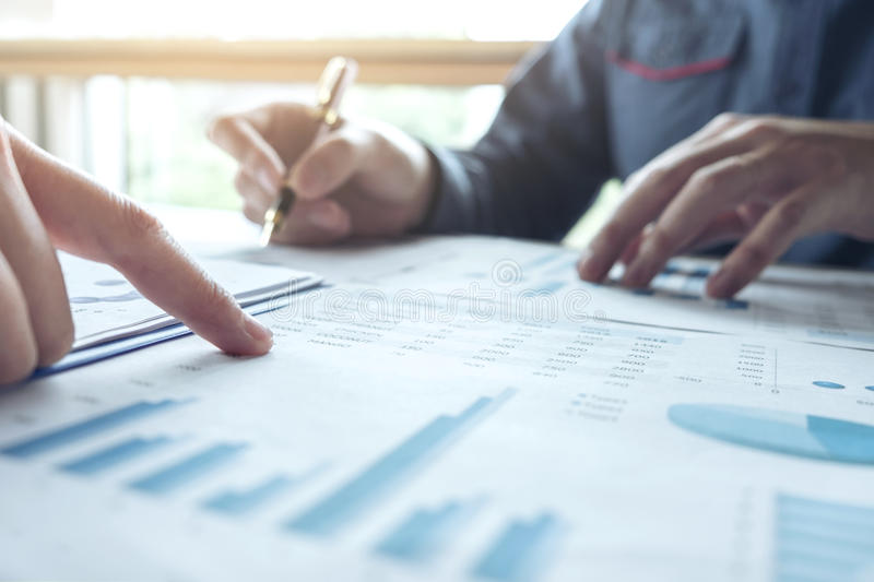 Two Business man or accountant working Financial investment, writing report Analyze business and market growth and pointing on. Financial document data graph royalty free stock images