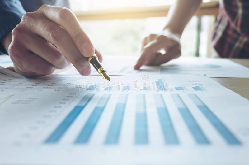 Two Business man or accountant working Financial investment, writing report Analyze business and market growth and pointing on. Financial document data graph stock image