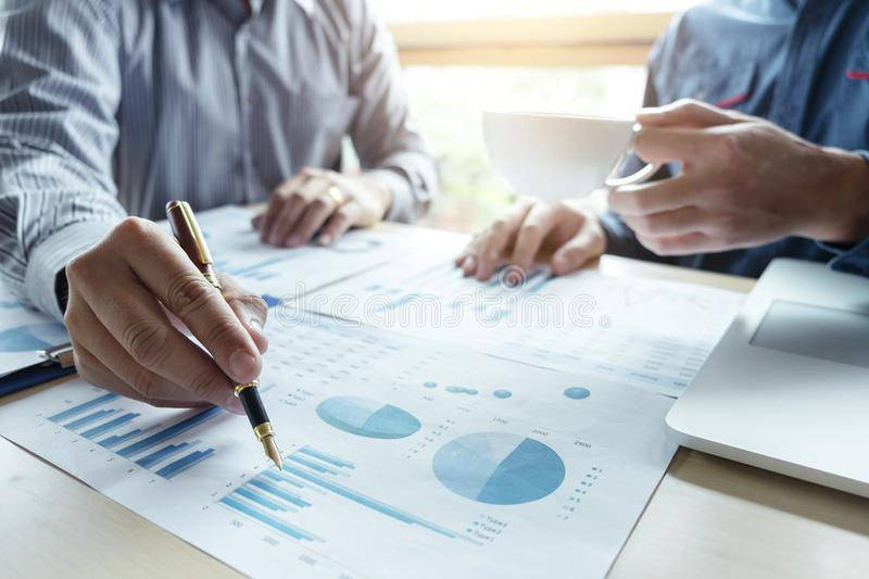 Two Business man or accountant working Financial investment, writing report Analyze business and market growth and pointing on. Financial document data graph royalty free stock photo