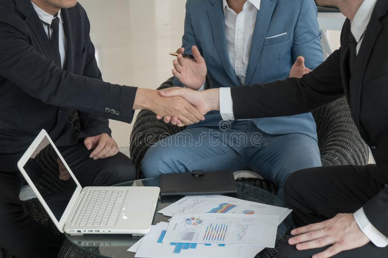 Two business man checking hand to success deal after meeting while another people applauding. Close-up royalty free stock photography