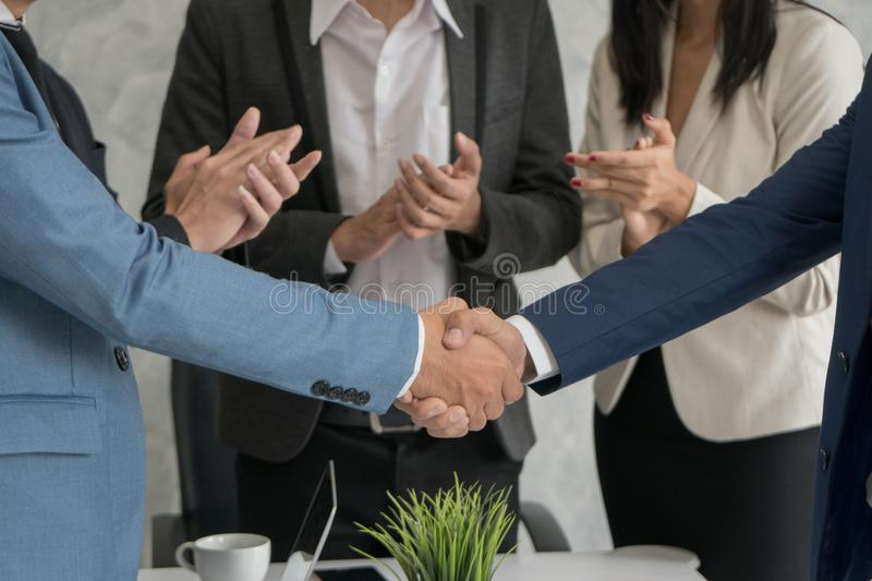 Two business man checking hand to success deal after meeting while another people applauding. Close-up stock image