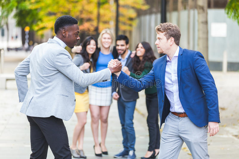 Two business men compete in arm wrestling. With some colleagues inciting them. They are a black men and a caucasian one wearing smart casual clothes. Challenge royalty free stock photo