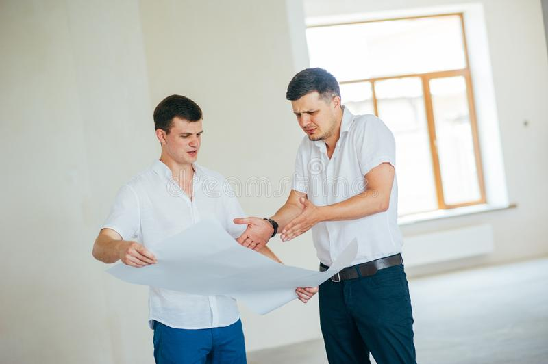 Two business men or engeners working and discussing plane house drawing during the construction and repair process indoor. stock image