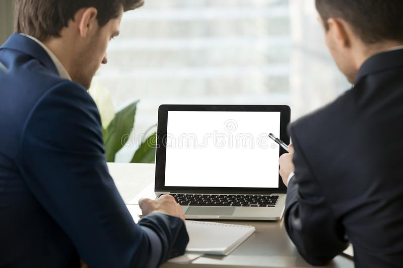Two business men looking at mock up blank laptop screen. royalty free stock image
