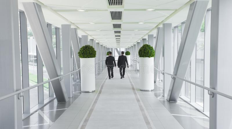 Two business men people walking in modern building royalty free stock images