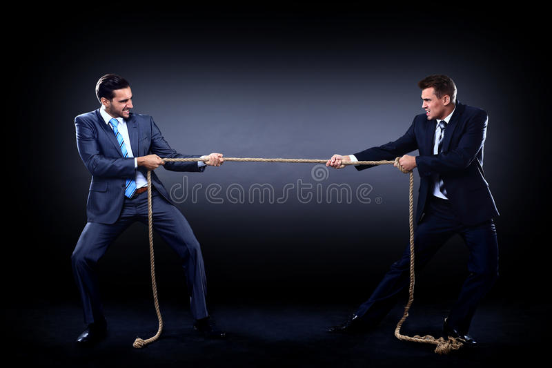 Two business men pulling rope in a competition stock photos