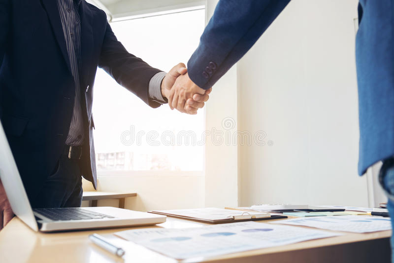 Two business men shaking hands during a meeting to sign agreement and become a business partner, enterprises, companies, confident. Success dealing, contract stock image