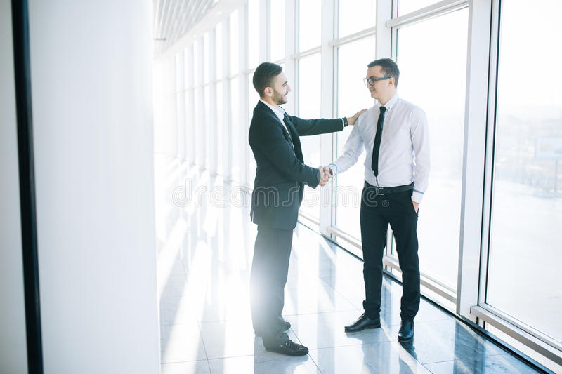 Two business men shaking hands in office royalty free stock photos