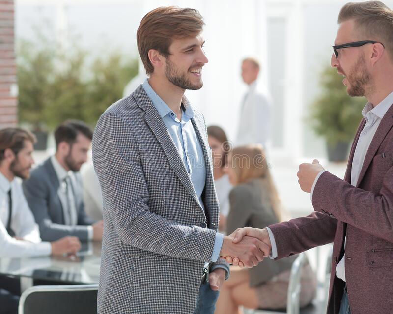 Two business men talking standing in the office. Photo with copy space royalty free stock image