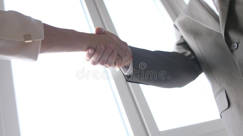 Two business partner shake hands when meeting between a man and woman in suit. Successful deal. royalty free stock photography