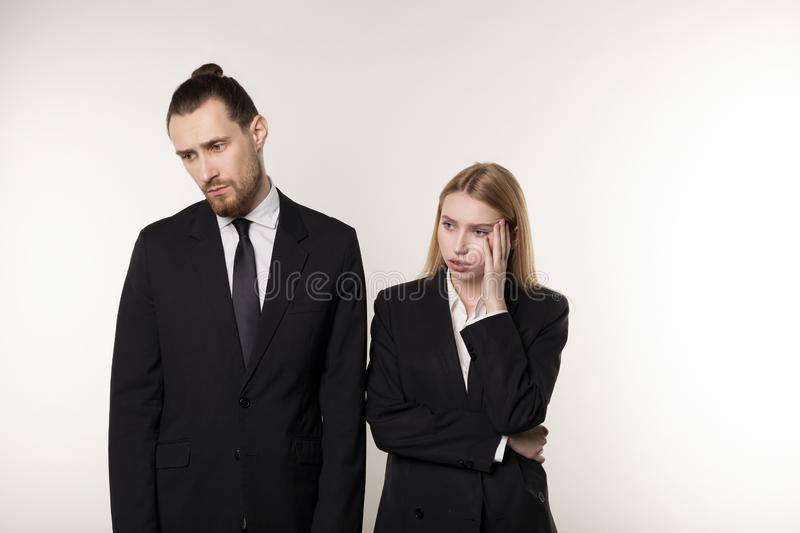 Two business partners in black suits, handsome bearded man and beautiful blonde woman shocked don`t know what to do stock photos