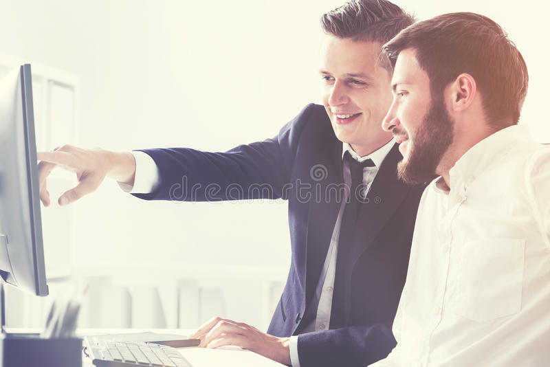 Two business partners pointing at computer screen stock photo