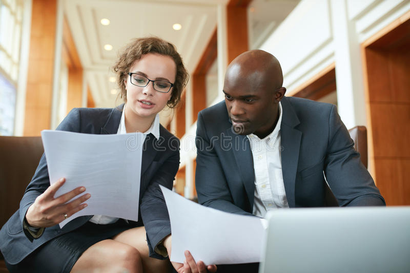 Two business partners sitting in cafe and discussing contract. royalty free stock photo