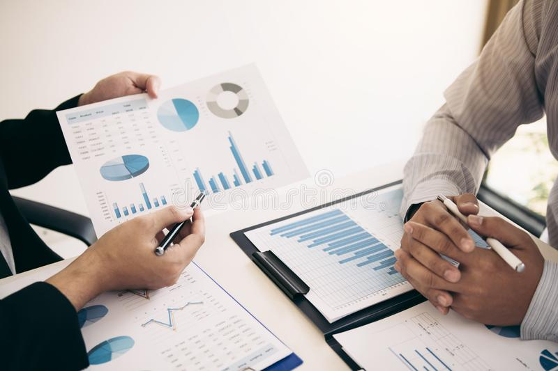 Two business partnership coworkers analysis strategy and gesturing with discussing a financial planning graph and company budget. During a budget meeting in royalty free stock photography