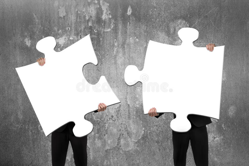 Two business people assembling white jigsaw puzzles with concrete wall. Two business people assembling blank white jigsaw puzzles with concrete wall background royalty free stock photo