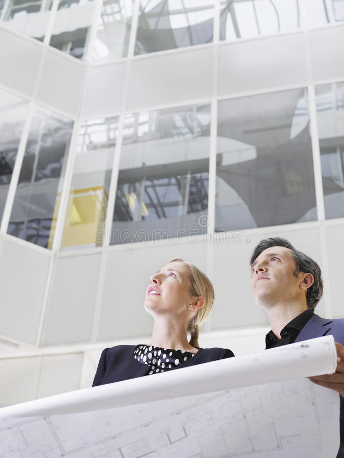 Two Business People With Blueprint In Office stock images