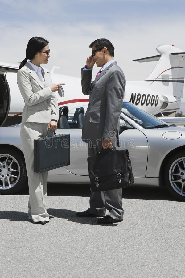 Two Business People Communicating. Full length of two business people communicating at airfield royalty free stock image